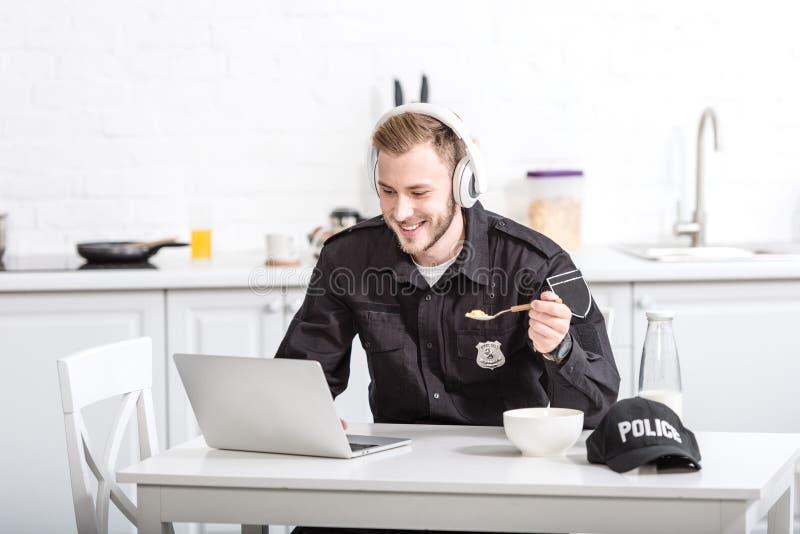 Όμορφος αστυνομικός που τρώει τα δημητριακά και που χρησιμοποιεί το lap-top στοκ φωτογραφία