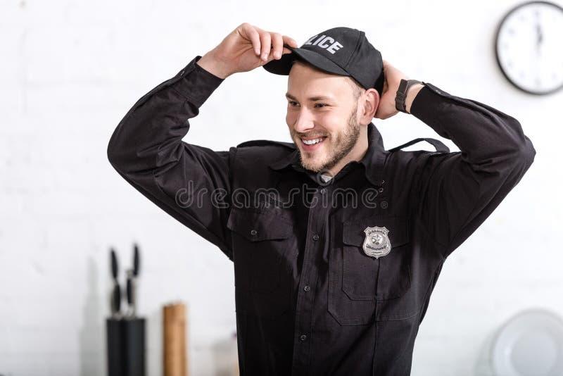 όμορφος αστυνομικός που χαμογελά και που βάζει στην ΚΑΠ στοκ εικόνα
