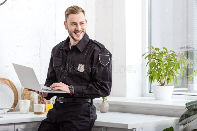 όμορφος αστυνομικός που χαμογελά και που χρησιμοποιεί το lap-top στοκ εικόνες με δικαίωμα ελεύθερης χρήσης