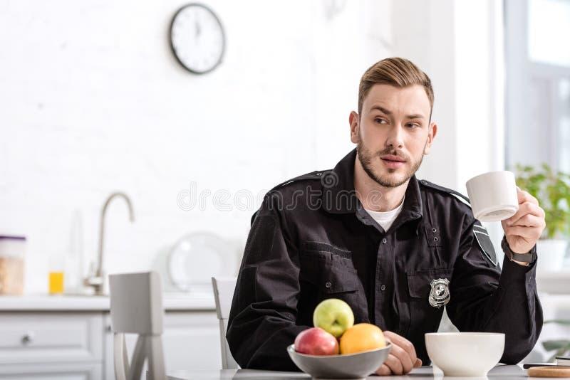 όμορφος αστυνομικός στη συνεδρίαση κουζινών, το φλυτζάνι εκμετάλλευσης του καυτού καφέ και την κατοχή του προγεύματος στοκ εικόνες με δικαίωμα ελεύθερης χρήσης