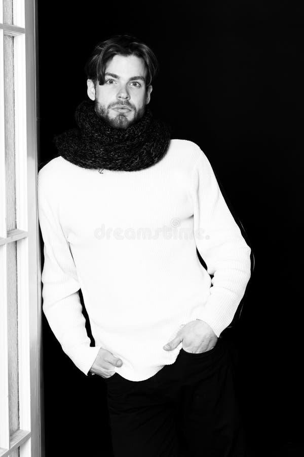 Όμορφος γενειοφόρος άτομο ή τύπος με τη γενειάδα στο πρόσωπο στο άσπρο πουλόβερ και πλεκτός στο μαύρο υπόβαθρο κοντά στο ξύλινο d στοκ φωτογραφίες