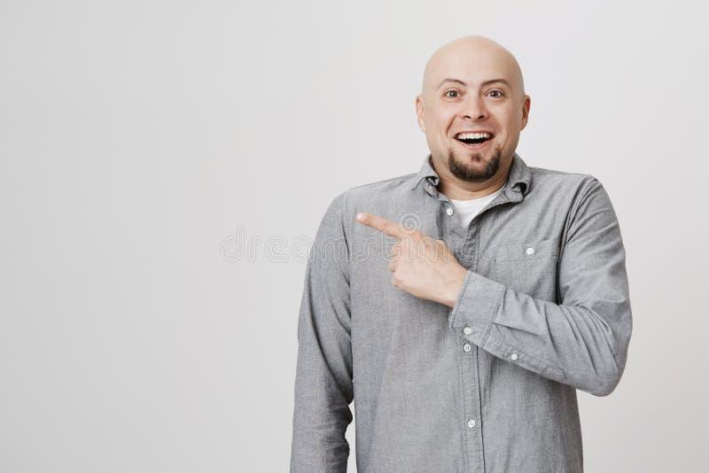 Όμορφος γενειοφόρος ενήλικος που φαίνεται κατάπληκτος και ευτυχής δείχνοντας το δάχτυλό του μακριά πέρα από το άσπρο υπόβαθρο Το  στοκ φωτογραφία