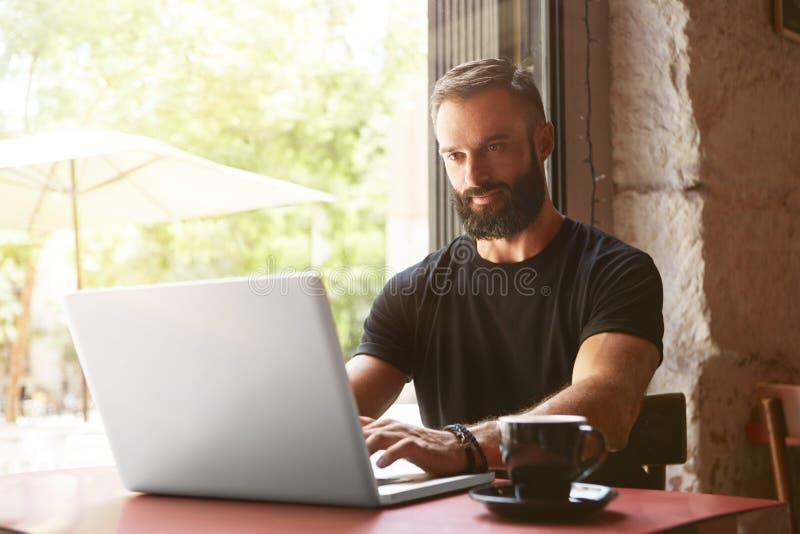 Όμορφος γενειοφόρος επιχειρηματίας που φορά το μαύρο ξύλινο επιτραπέζιο αστικό καφέ lap-top μπλουζών λειτουργώντας Νέο σημειωματά στοκ φωτογραφία με δικαίωμα ελεύθερης χρήσης