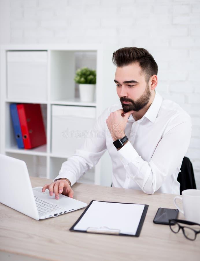 Όμορφος γενειοφόρος επιχειρηματίας που χρησιμοποιεί τον υπολογιστή στην αρχή στοκ φωτογραφία με δικαίωμα ελεύθερης χρήσης