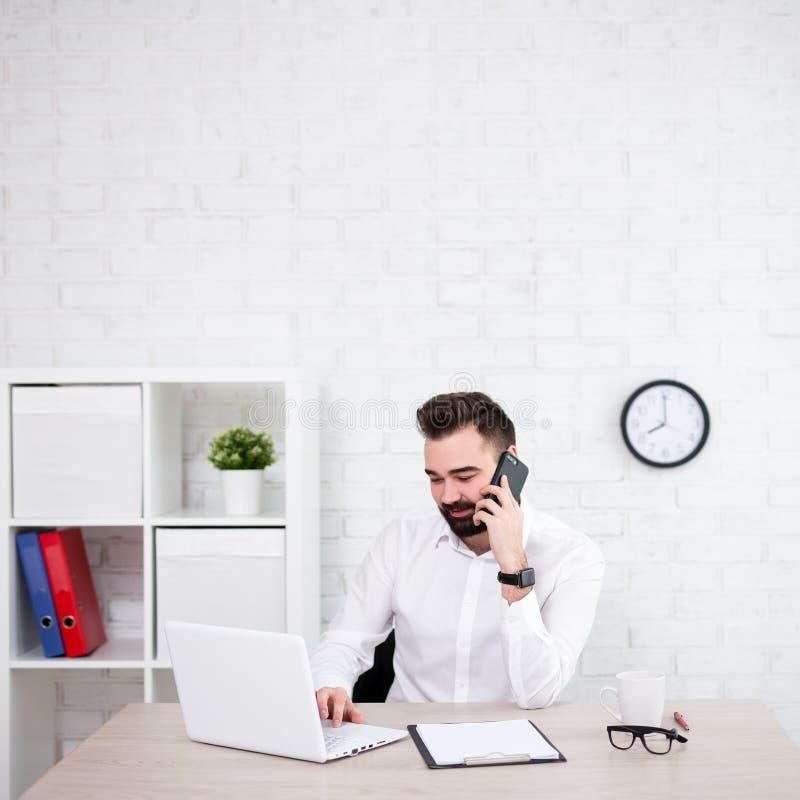 Όμορφος γενειοφόρος επιχειρηματίας που χρησιμοποιεί τον υπολογιστή και την ομιλία τηλεφωνικώς στην αρχή στοκ εικόνα με δικαίωμα ελεύθερης χρήσης