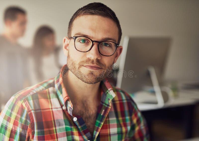 Όμορφος γενειοφόρος εργαζόμενος στο μικρό γραφείο στοκ εικόνα