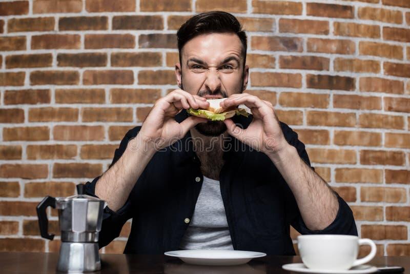 όμορφος γενειοφόρος νεαρός άνδρας που τρώει το σάντουιτς και που πίνει τον καφέ στοκ εικόνες