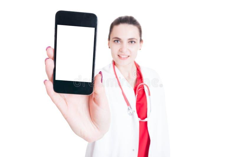 Όμορφος γιατρός γυναικών που παρουσιάζει smartphone με την κενή οθόνη στοκ εικόνα με δικαίωμα ελεύθερης χρήσης