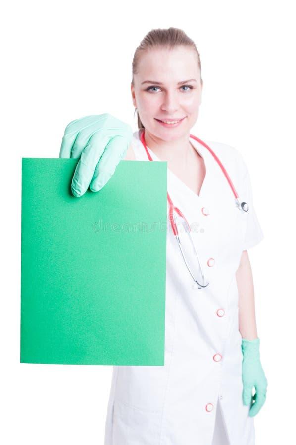 Όμορφος γιατρός γυναικών που χαμογελά και που κρατά ένα κενό χαρτόνι στοκ εικόνες