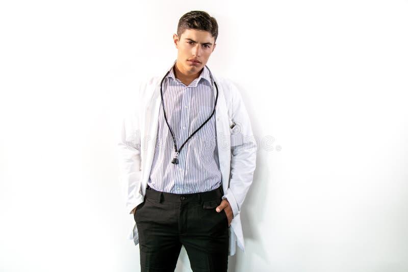 Όμορφος γιατρός που φορούν το άσπρο παλτό εργαστηρίων και στηθοσκόπιο που στέκεται στο απομονωμένο κλίμα που εξετάζει τη κάμερα στοκ φωτογραφία με δικαίωμα ελεύθερης χρήσης