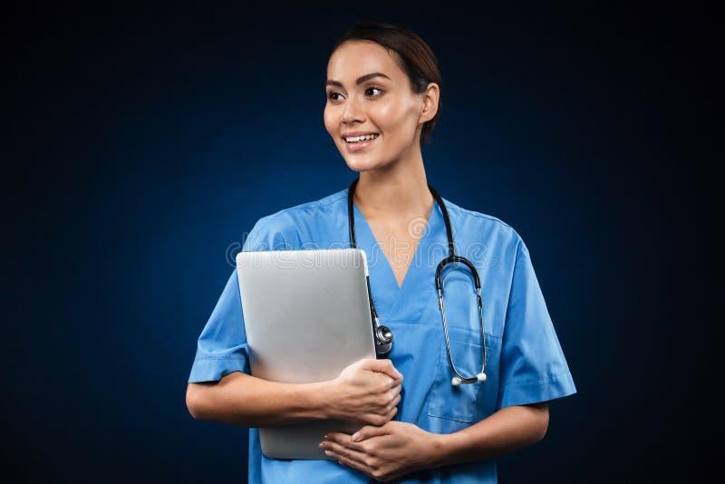 Όμορφος γυναικείος γιατρός με το φορητό προσωπικό υπολογιστή που κοιτάζει κατά μέρος στοκ εικόνα