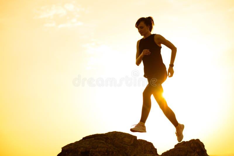 Όμορφος δρομέας γυναικών που πηδά από το βράχο στο ίχνος βουνών στο καυτό θερινό ηλιοβασίλεμα Αθλητισμός και ενεργός τρόπος ζωής στοκ εικόνα