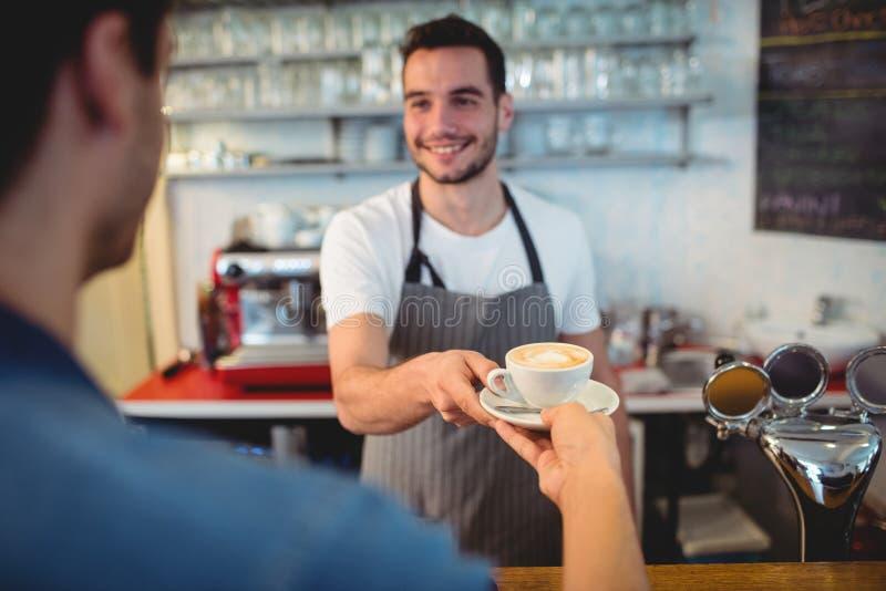 Όμορφος εξυπηρετώντας καφές σερβιτόρων στον αρσενικό πελάτη στην καφετέρια στοκ εικόνα