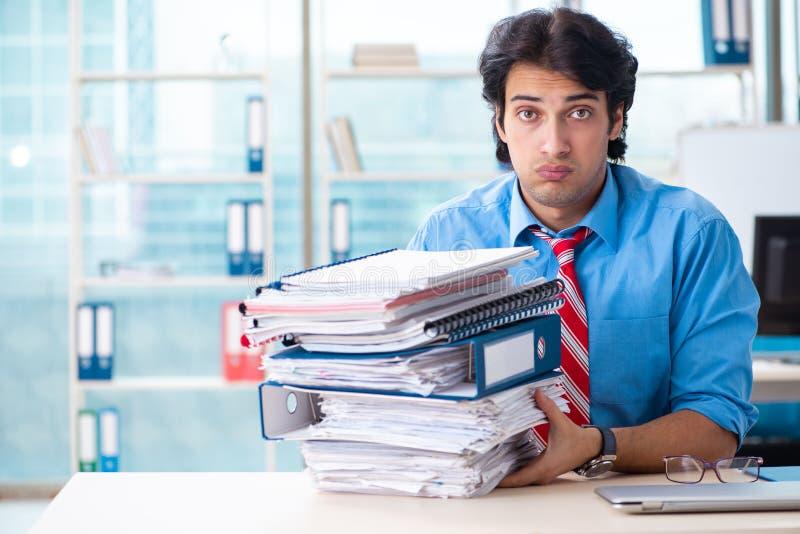 Όμορφος επιχειρηματίας δυστυχισμένος με την υπερβολική εργασία στο γραφείο στοκ φωτογραφία