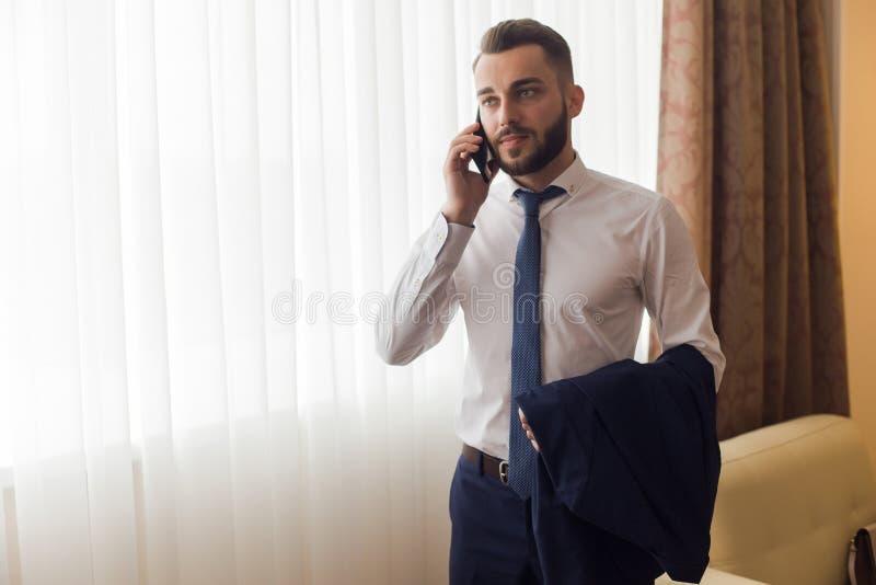 Όμορφος επιχειρηματίας που καλεί από το δωμάτιο ξενοδοχείου στοκ εικόνες
