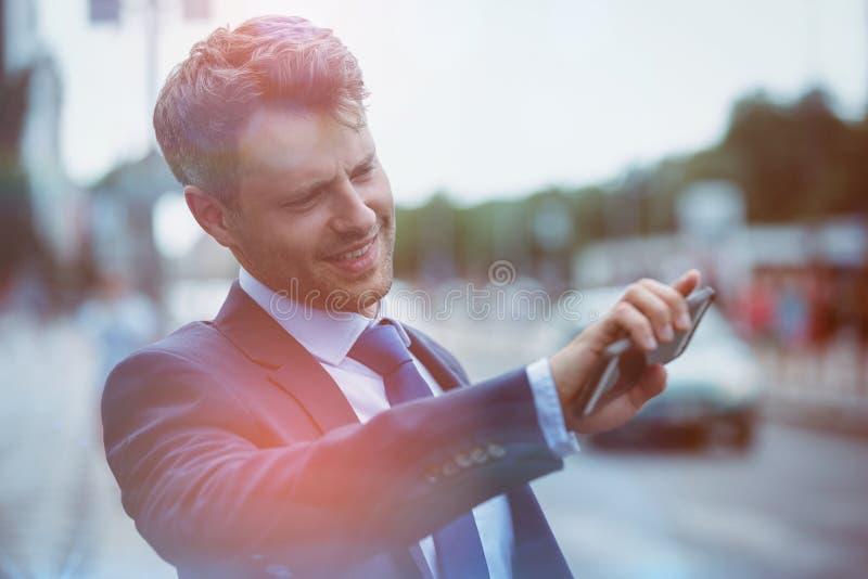 Όμορφος επιχειρηματίας που κρατά το κινητό τηλέφωνο και που χαιρετά το ταξί στοκ εικόνες με δικαίωμα ελεύθερης χρήσης