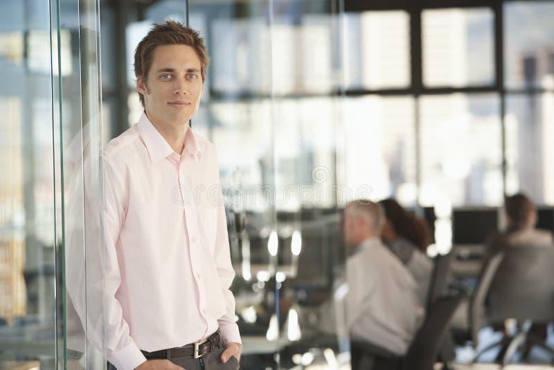 Όμορφος επιχειρηματίας που κλίνει στην πόρτα γυαλιού γραφείων στοκ φωτογραφία
