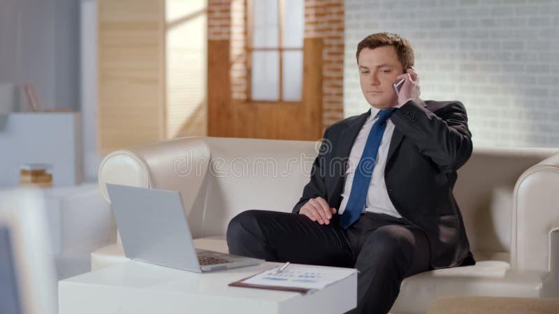 Όμορφος επιχειρηματίας που μιλά στο τηλέφωνο, που κάθεται άνετα στον καναπέ στην αρχή στοκ εικόνες