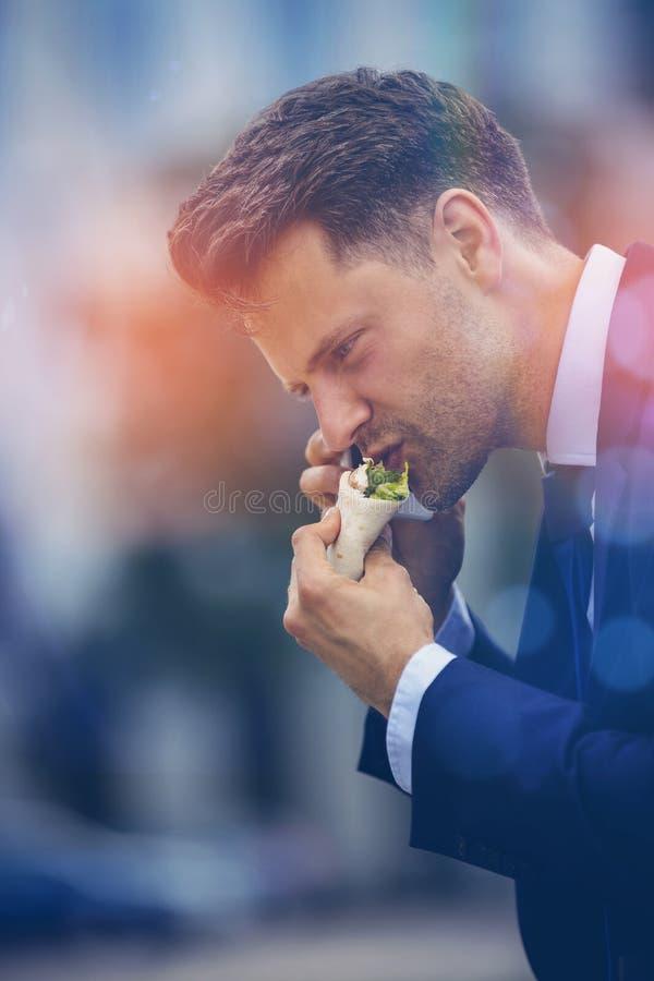 Όμορφος επιχειρηματίας που τρώει τα πρόχειρα φαγητά και που μιλά στο τηλέφωνο στοκ εικόνες