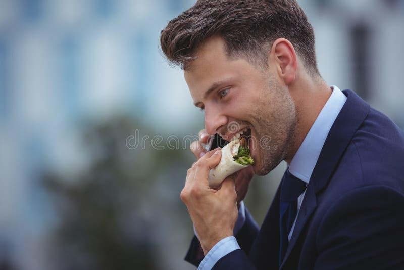 Όμορφος επιχειρηματίας που τρώει τα πρόχειρα φαγητά στοκ εικόνα με δικαίωμα ελεύθερης χρήσης