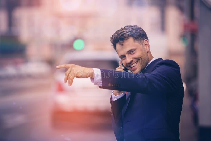Όμορφος επιχειρηματίας που χαιρετά το ταξί παίρνοντας το τηλέφωνο στοκ εικόνα