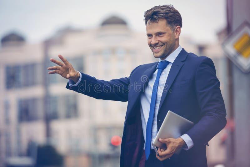 Όμορφος επιχειρηματίας που χαιρετά το ταξί στοκ εικόνες