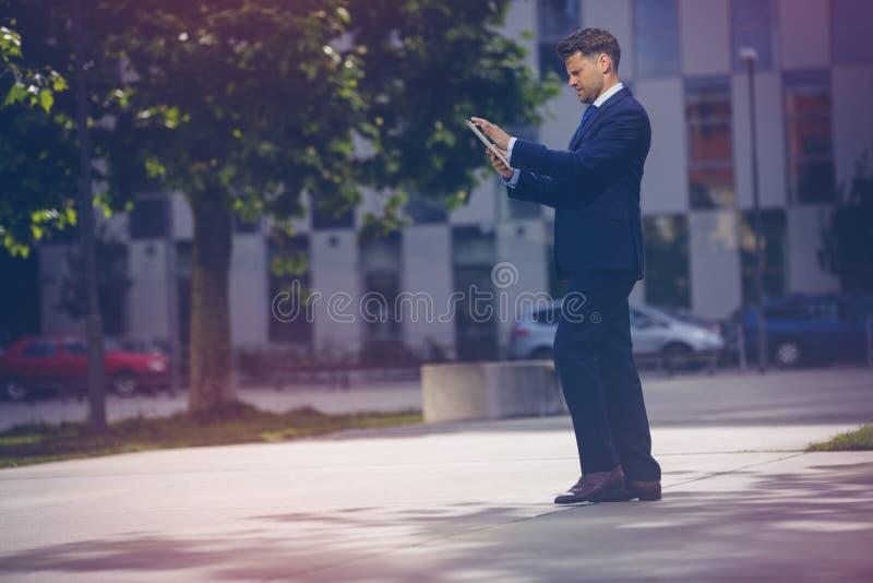 Όμορφος επιχειρηματίας που χρησιμοποιεί την ψηφιακή ταμπλέτα στο δρόμο ενάντια στο γραφείο στοκ φωτογραφία