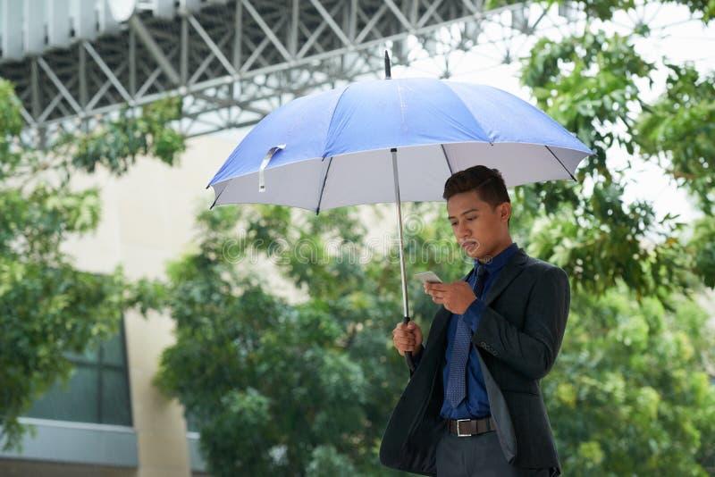 Όμορφος επιχειρηματίας που χρησιμοποιεί Smartphone στη βροχή στοκ εικόνες