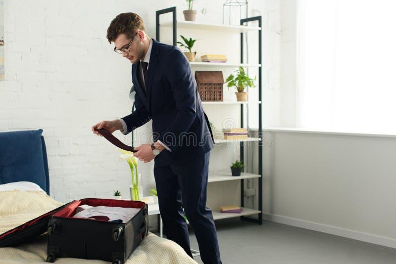 όμορφος επιχειρηματίας στην τσάντα ταξιδιού συσκευασίας κοστουμιών στοκ φωτογραφία