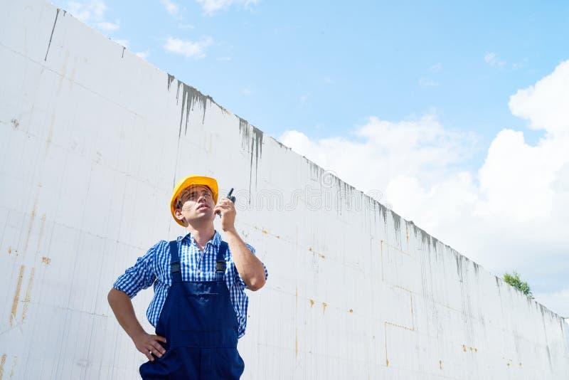 Όμορφος εργάτης οικοδομών που χρησιμοποιεί Walkie-Talkie στοκ φωτογραφία με δικαίωμα ελεύθερης χρήσης