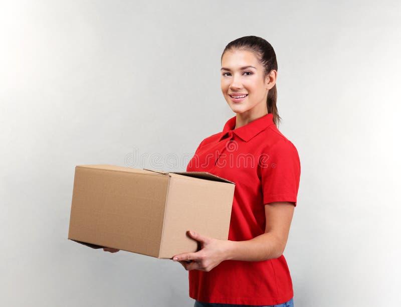 Όμορφος εργαζόμενος αποθηκών εμπορευμάτων με το κουτί από χαρτόνι στοκ φωτογραφία