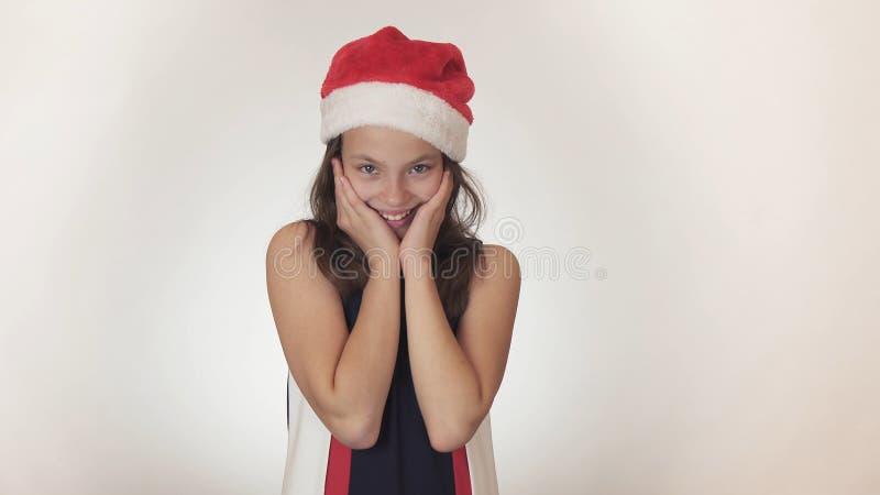 Όμορφος ευτυχής έφηβος κοριτσιών σε ένα καπέλο Άγιου Βασίλη που φαντάζεται και που θέτει συναισθηματικά στο άσπρο υπόβαθρο στοκ φωτογραφίες με δικαίωμα ελεύθερης χρήσης