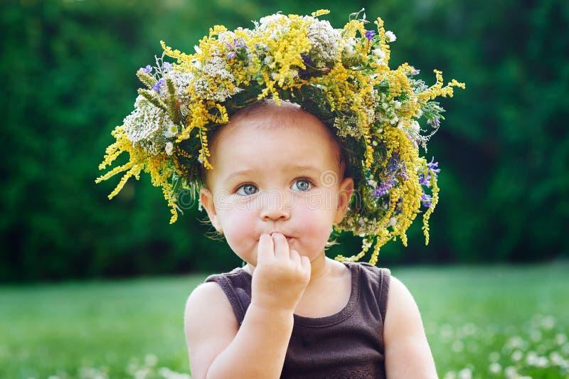 Όμορφος ευτυχής λίγο κοριτσάκι σε ένα στεφάνι σε ένα λιβάδι στη φύση στοκ εικόνες