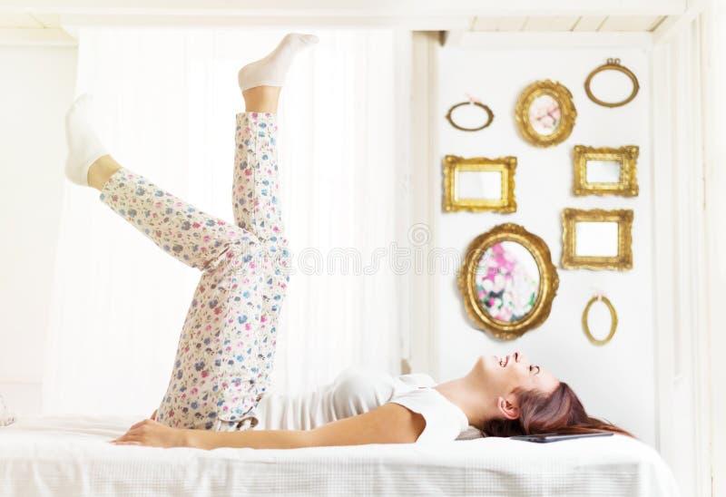Όμορφος, ευτυχής, γυναίκα που βάζει στο κρεβάτι σε ένα φωτεινό δωμάτιο στοκ εικόνες