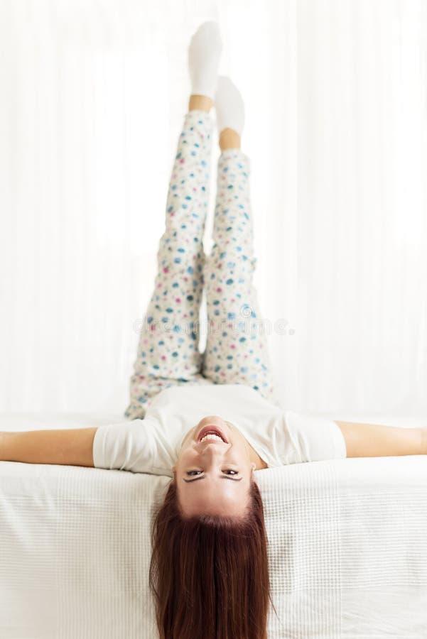 Όμορφος, ευτυχής, γυναίκα που βάζει στο κρεβάτι σε ένα φωτεινό δωμάτιο στοκ εικόνα