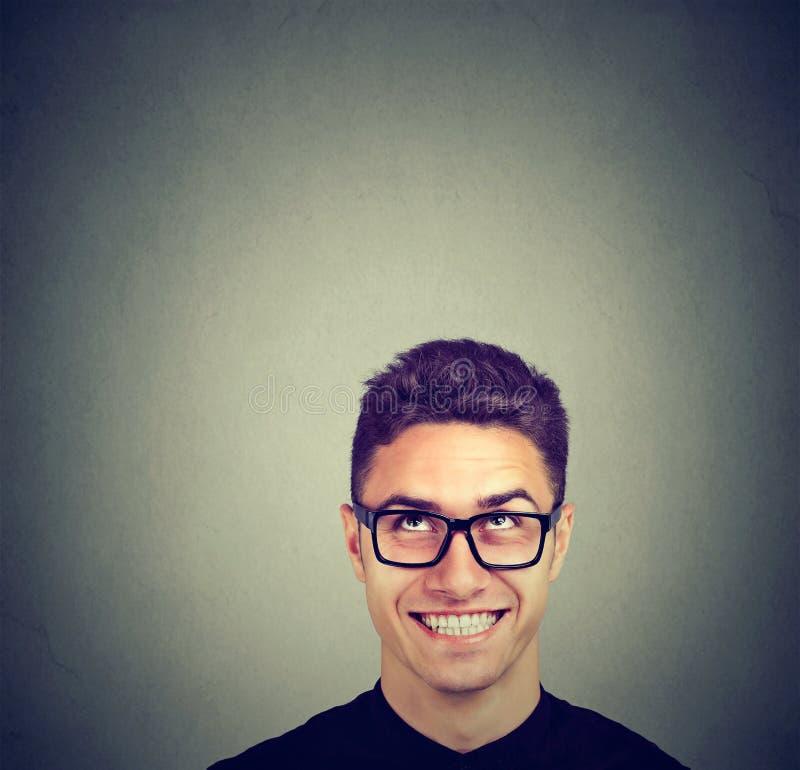 Όμορφος ευτυχής νεαρός άνδρας στα γυαλιά που ανατρέχει στοκ φωτογραφία