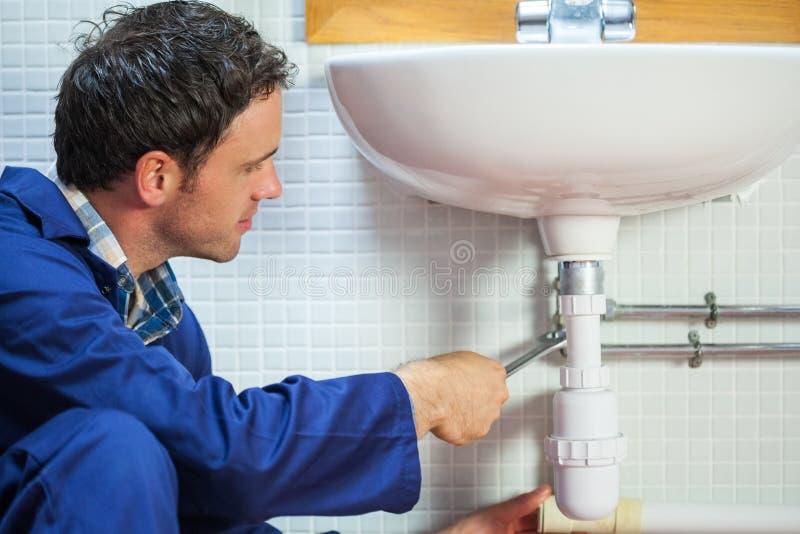 Όμορφος ευτυχής υδραυλικός που επισκευάζει το νεροχύτη στοκ εικόνα με δικαίωμα ελεύθερης χρήσης
