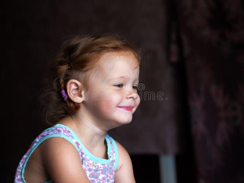 Όμορφος ευτυχής χαριτωμένος λίγο redhead κορίτσι χαμογελά ειλικρινά και γελά με ένα μαλακό φως από τον τρόπο ζωής παραθύρων στοκ εικόνα