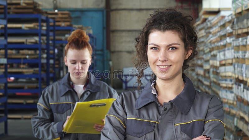 Όμορφος εύθυμος θηλυκός βιομηχανικός εργάτης που χαμογελά στη κάμερα στοκ εικόνα με δικαίωμα ελεύθερης χρήσης