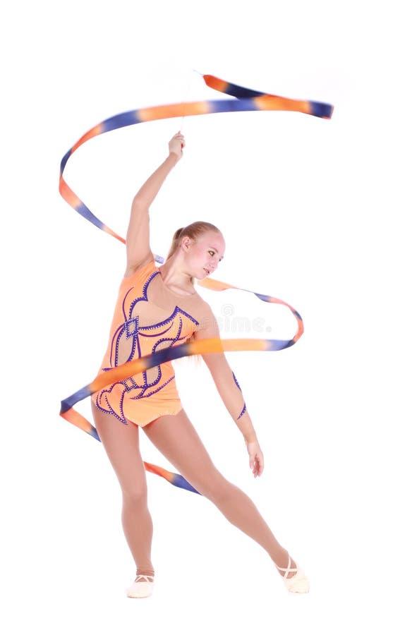 Όμορφος εύκαμπτος gymnast κοριτσιών με μια γυμναστική κορδέλλα πέρα από το whi στοκ εικόνα