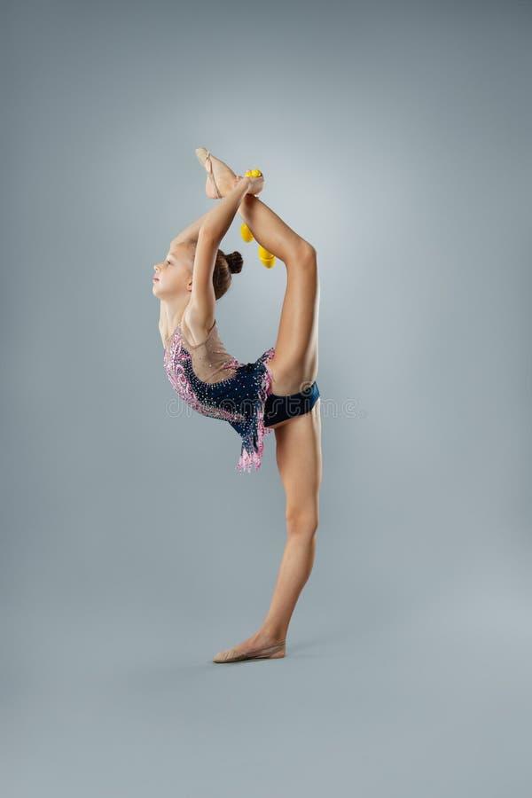 Όμορφος εύκαμπτος gymnast στην αθλητική εξάρτηση εκτελεί ένα στοιχείο της ρυθμικής γυμναστικής στοκ φωτογραφία με δικαίωμα ελεύθερης χρήσης