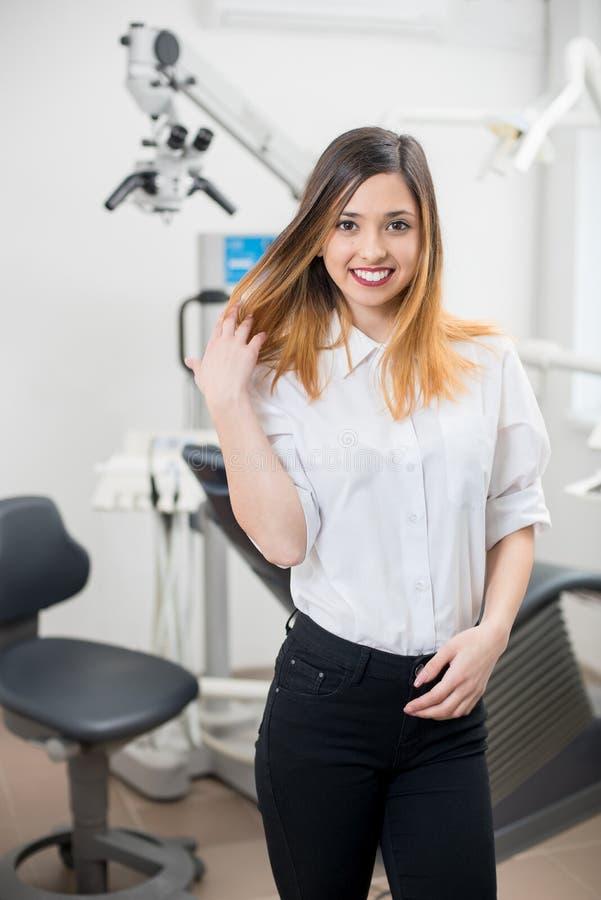 Όμορφος θηλυκός ασθενής με τα τέλεια άσπρα δόντια που χαμογελά μετά από τη θεραπεία στη σύγχρονη οδοντική κλινική οδοντιατρική στοκ φωτογραφίες