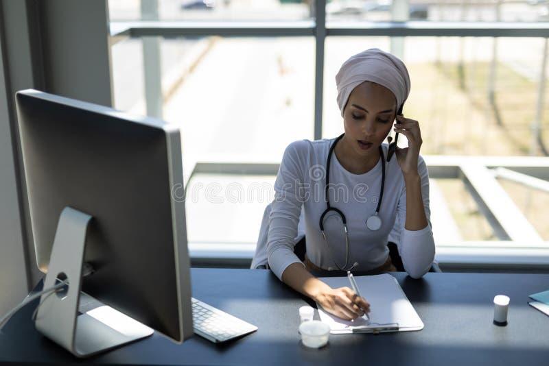 Όμορφος θηλυκός γιατρός αναμιγνύω-φυλών που μιλά στο κινητό τηλέφωνο γράφοντας στην περιοχή αποκομμάτων στοκ εικόνες με δικαίωμα ελεύθερης χρήσης