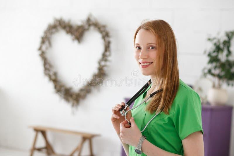Όμορφος θηλυκός καρδιολόγος γιατρών ή νευρολόγος και μορφή καρδιών στο υπόβαθρο Υγειονομική περίθαλψη, υγιής έννοια καρδιών στοκ φωτογραφία