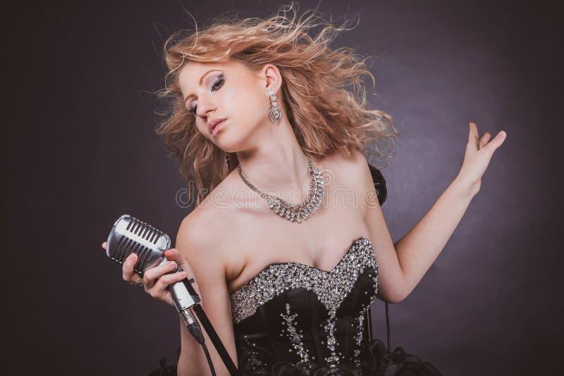 Όμορφος θηλυκός τραγουδιστής στο μαύρο φόρεμα συναυλίας που εκτελεί μια μουσική σύνθεση στοκ εικόνες με δικαίωμα ελεύθερης χρήσης