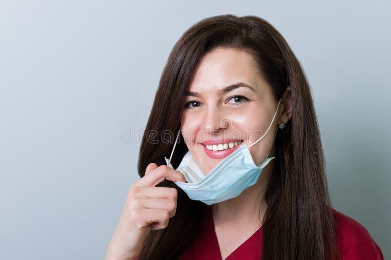 Όμορφος θηλυκός οδοντίατρος που αφαιρεί τη μάσκα και το χαμόγελο στοκ φωτογραφία