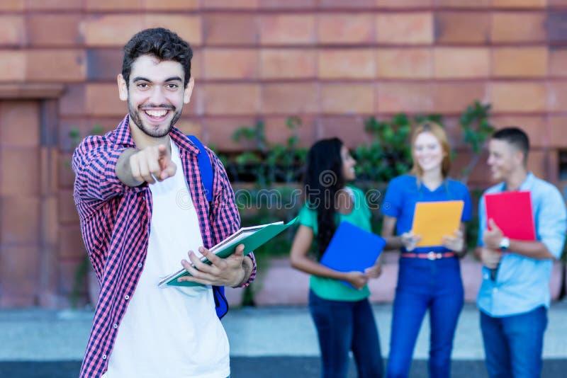 Όμορφος ισπανικός άνδρας σπουδαστής με την ομάδα σπουδαστών στοκ εικόνες