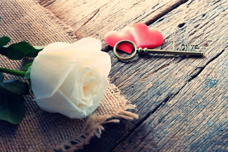 Όμορφος καθαρός άσπρος αυξήθηκε με το κλειδί μορφής αγάπης στην κόκκινη καρδιά σατέν δύο Μαλακός τόνος για ρομαντικό Valentine& x στοκ φωτογραφία