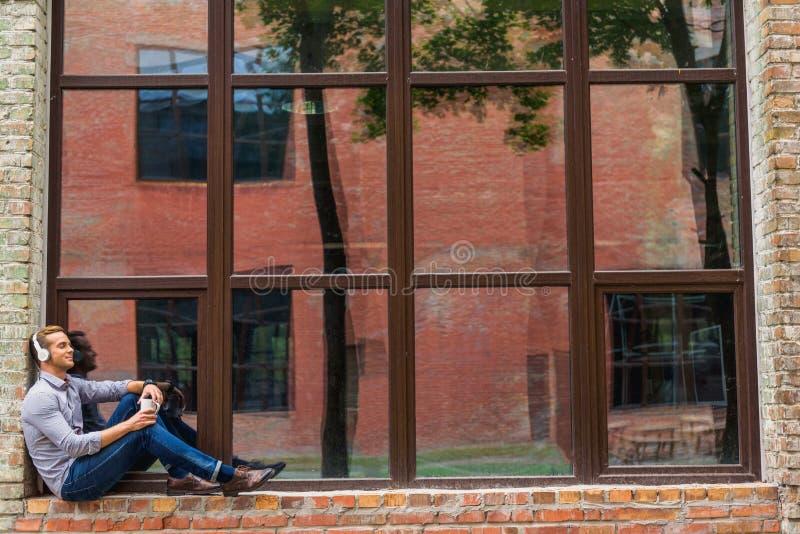 Όμορφος καφές κατανάλωσης ατόμων έξω από το κτίριο γραφείων στοκ φωτογραφία με δικαίωμα ελεύθερης χρήσης