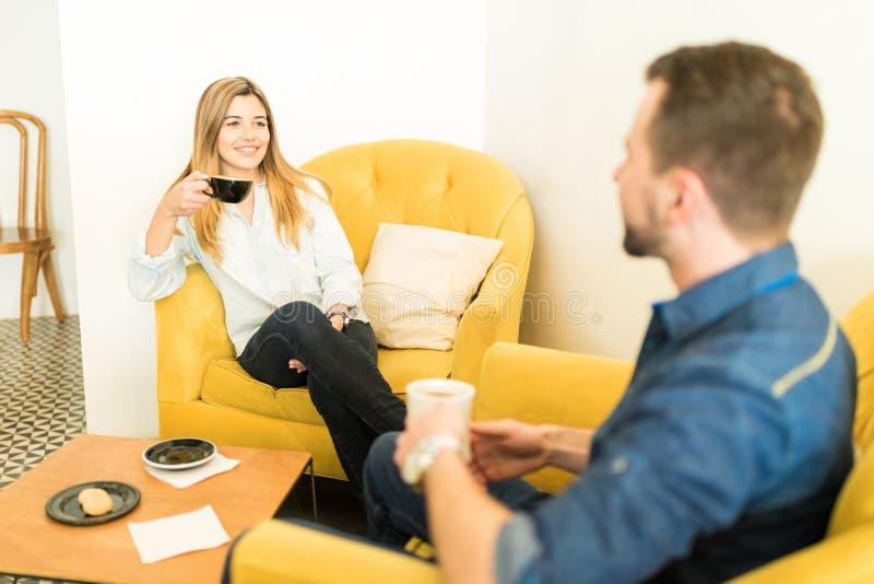 Όμορφος καφές κατανάλωσης γυναικών κατά μια ημερομηνία στοκ εικόνες